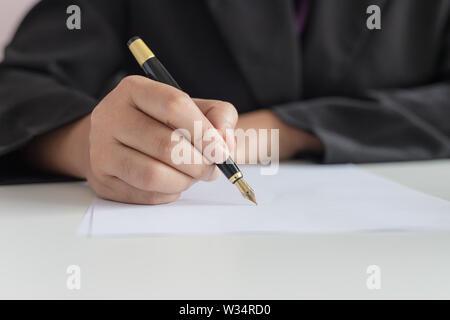 Immagine ravvicinata di mano business donna utilizzando la penna per scrivere sul libro bianco selezionare focus leggera profondità di campo Foto Stock