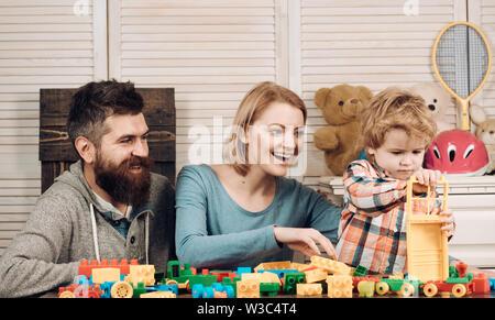 Il padre e la madre con bambino gioca costruttore. infanzia felice. Cura e sviluppo. La famiglia felice e giorno. Ragazzino con papà e mamma. ACCESA Foto Stock