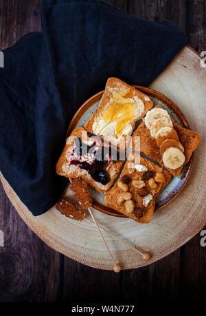 Una sana prima colazione al mattino con diversi tipi di pane tostato e zucchero di canna in legno rustico sfondo. Foto Stock