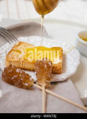 Close-up di una deliziosa colazione con glassato al miele e toast vintage Dettagli in cucina. Foto Stock