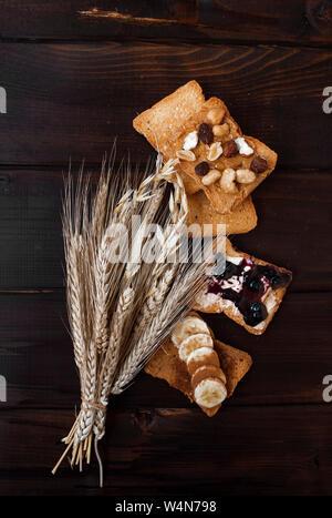 Un sano di diversi tipi di pane tostato di mattina con i chicchi di grano e su sfondo di legno. Foto Stock
