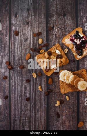 Close-up della mattina toast con diversi tipi di condimenti su sfondo di legno. Foto Stock