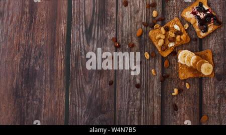 Topview della sana colazione con pane tostato , i dadi, miele, marmellata e banana su sfondo di legno. Foto Stock