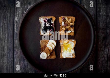 Vista dall'alto di diversi condimenti su toast , Burro di arachidi , banana, marmellata e miele su sfondo di legno. Foto Stock