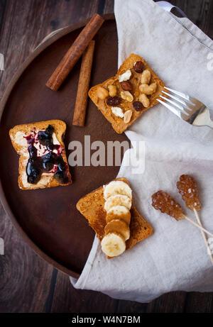 La colazione piatto in legno con diversi tipi di ripristino su pane tostato con la cannella e lo zucchero di canna su sfondo di legno. Foto Stock