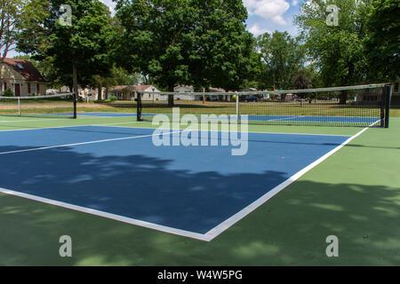 Sport ricreativo di pickleball corte nel Michigan, Stati Uniti d'America cercando in corrispondenza di un vuoto azzurro e verde nuovo tribunale in un parco all'aperto. Vista di massa. Foto Stock