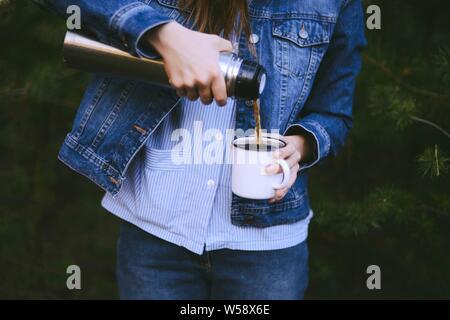 Traveler ragazza versando il tè dalla tazza thermos, all'esterno. Giovane donna bere il tè in tazza. Viaggi a tema. Donna versando una bevanda calda in tazza da thermos. Gi Foto Stock