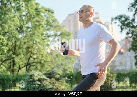 Maturo uomo sportivo in esecuzione. Persone di mezza età maschio con bicchieri corre attraverso il parco della città con le cuffie, spazio di copia Foto Stock