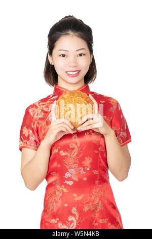 Bella donna cinese che indossa un Cheongsam o Chipao tenendo una torta della luna il cibo tradizionale della vacanza cinese di metà autunno Festival isolato Foto Stock