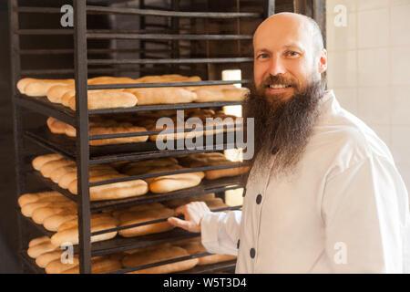 Ritratto di felice giovane adulto baker con barba lunga in bianco uniforme in piedi nel suo ambiente di lavoro e ripiani porta con il pane al forno manufactu Foto Stock