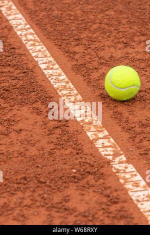 Palla da tennis che giace vicino la linea bianca sul campo da tennis sfondo Foto Stock