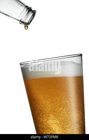 Bottiglia vuota con l'ultima goccia che cade in una spillata di fresco bicchiere pieno di birra Foto Stock