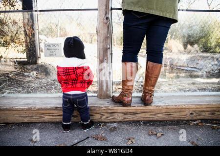 Vista posteriore del ragazzino e la madre in piedi accanto a ciascun altro Foto Stock