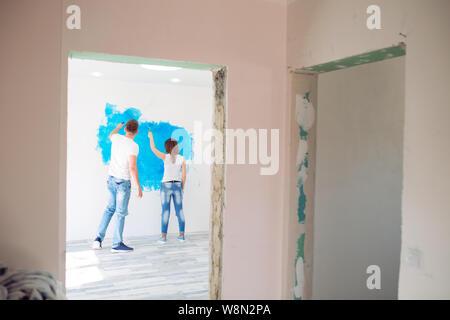 Coppia felice pittura pareti nella loro nuova casa pronta per vivere insieme. Foto Stock