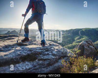 L'uomo turistico con gamba fissa rende passo sulla collina rocciosa con l aiuto di avambraccio stampelle. Foto Stock