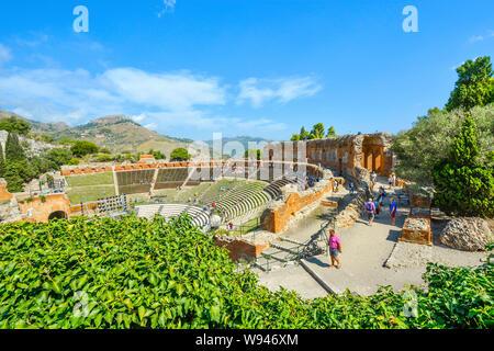 I turisti che visitano l'antico teatro greco nel resort costiero città di Taormina, Italia, sulla costa dell'isola di Sicilia. Foto Stock