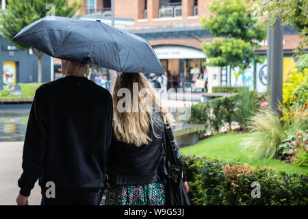 Un paio di camminare insieme sotto un ombrello sotto la pioggia Foto Stock
