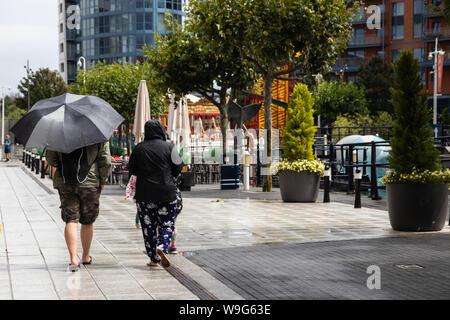 Un giovane a piedi sotto la pioggia, la signora è in possesso di un ombrello Foto Stock