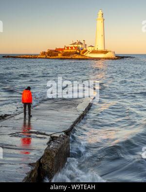 Un uomo si erge sulla St Mary's Island Causeway mentre il sole illumina St Mary's faro sulla costa di Whitley Bay in Tyneside. Foto Stock