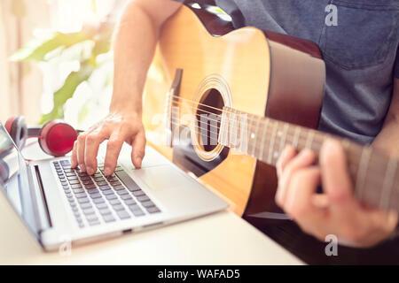 Musicista suonare la chitarra acustica e la registrazione di musica sul computer o apprendimento ufm lezione online Foto Stock