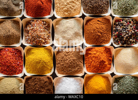 Vari tipi di spezie orientali ed erbe aromatiche. Vista sopra con spezie sfondo. Piatto di laici spezie colorate in un pattern. Gli ingredienti della cucina telaio. Foto Stock