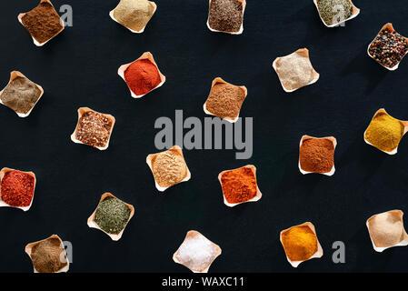 Varietà di erbe e spezie in ciotole, un pattern su uno sfondo nero. Piatto di laici condimenti sfondo. Al di sopra di vista con sapori. Telaio di cottura. Foto Stock