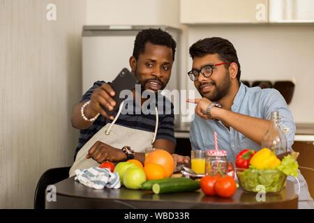 Due multirazziale amici studenti seduti a tavola tenendo selfie insieme durante la preparazione di insalata di verdure e succhi di frutta in ostello. Ragazzo africano con i Foto Stock