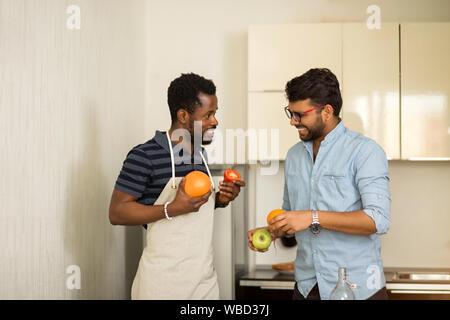 Due gli studenti di sesso maschile in abiti casual andando al frullato di cottura in piedi in cucina di hostel, tenendo pompelmo, arancio, Apple, pomodoro in mani, allegria Foto Stock