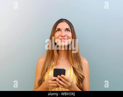Bella ragazza cerca la copia spazio mentre texting su smart phone. Foto Stock
