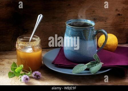 Tisana contro il freddo con salvia fresca, menta, miele e limone in una tazza di colore blu su un rustico di legno, il concetto di salute, casa rimedi per rafforzare th Foto Stock