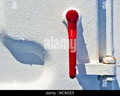Maniglia rossa close up su bianco metallizzato porta di una nave traghetto. Foto Stock