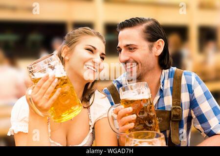 Coppia giovane in tradizionali bavaresi Tracht - Dirndl e lederhosen - in una tenda di birra al Oktoberfest godendo le loro birre e flirtare con ciascun ot Foto Stock