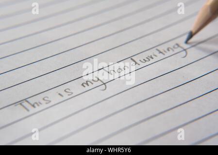 """Scrittura a mano utilizzando una matita su un foglio di carta.scrivere """" questa è la mia calligrafia"""" Foto Stock"""