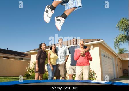 Felice famiglia americana africana guardando ragazzo salta sul trampolino Foto Stock