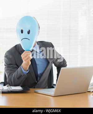 Ritratto di un giovane imprenditore tenendo triste di fronte palloncino a scrivania da ufficio Foto Stock