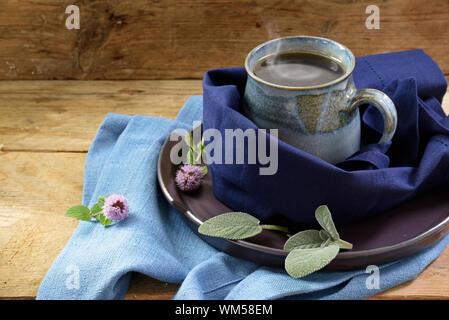 Tazza fumante di tè alle erbe contro il freddo avvolto in un panno blu su legno rustico, erbe aromatiche come la salvia e menta per il sistema immunitario e flu prevenzione Foto Stock