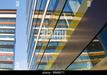 Facciata moderna degli edifici con le linee, i colori e il pattern si riflette in una parete di vetro contro il cielo blu Foto Stock