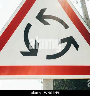 Primo piano della nuova rotatoria del segno che indica che una rotatoria è più avanti sulla strada Foto Stock