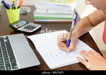 Giovani schoolgirl sta facendo i compiti con la matematica accanto a un computer portatile, calcolatrice e libri sulla sua scrivania in camera sua Foto Stock