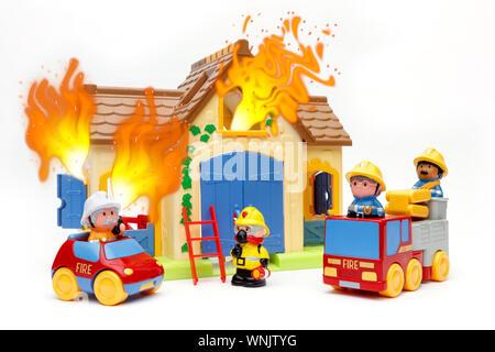Toy vigili del fuoco di affrontare un giocattolo di casa che è sul fuoco, con fiamme provenienti da windows, girato su sfondo bianco Foto Stock