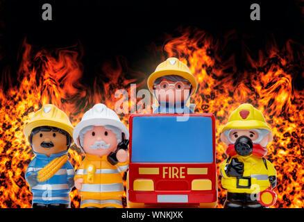 Una linea di 3 toy vigili del fuoco permanente per l'attenzione e un incendio del motore, con fiamme bruciare in background Foto Stock