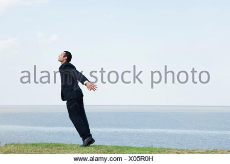 Imprenditore in piedi in punta di piedi dal mare prendendo un respiro profondo Foto Stock