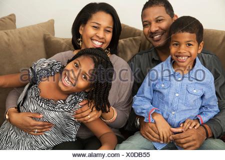Ritratto di metà adulto genitori con figlio e figlia sul divano Foto Stock