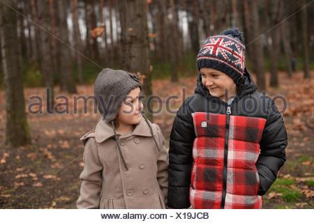 Fratello (6-7) e sorella (4-5) passeggiate in foresta Foto Stock