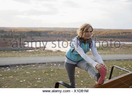 Runner donna allungamento della gamba sul banco in autunno parco affacciato sul lago Foto Stock