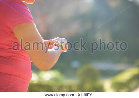 Ritagliato vista laterale di donna matura di controllo orologio da polso Foto Stock