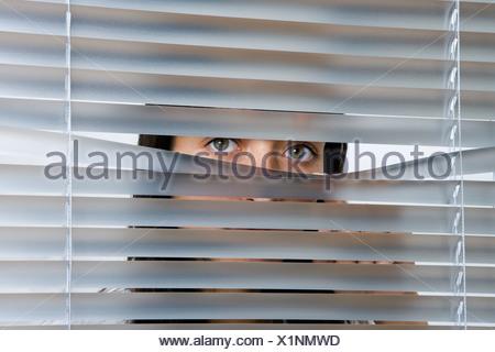 Una giovane donna del peering attraverso le veneziane Foto Stock