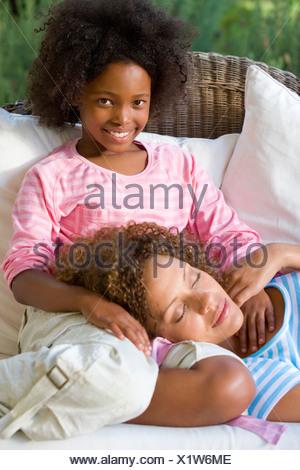 Madre dormendo nella mia figlia lap sul divano Foto Stock