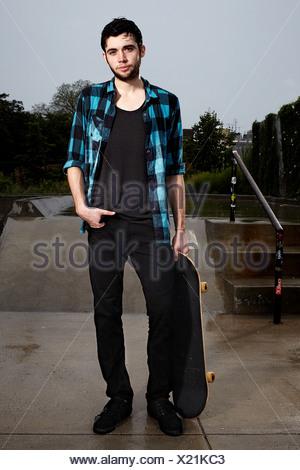 Giovane guidatore di skateboard in skate park, ritratto Foto Stock
