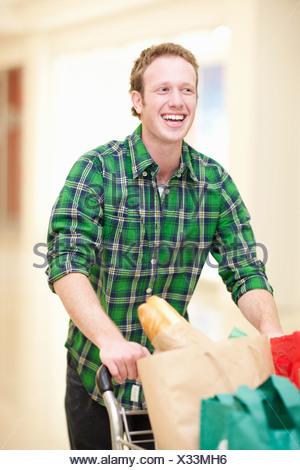 L'uomo spingendo il carrello di shopping nel centro commerciale Foto Stock